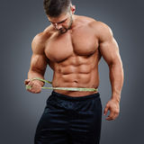 Bodybuilder measuring waist with tape measure. Muscular bodybuilder with six pack abs tries to measure his waist by himself. Sexy athletic young man looking at Stock Photography