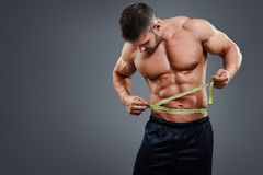 Bodybuilder measuring waist with tape measure. Muscular sports man measuring his waist with tape measure isolated over gray background. Bodybuilder waist measure Royalty Free Stock Image