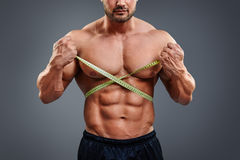 Bodybuilder measuring waist with tape measure Royalty Free Stock Photos