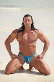 Bodybuilder meditating. On the sand with eyes closed Stock Photography