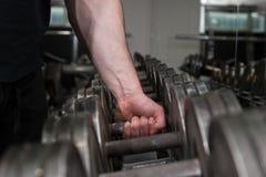 Bodybuilder met zijn sterk, groot wapen die zwarte metaaldomoor van het rek in een gymnastiek opnemen Geschiktheid en gymnastiekd stock foto's