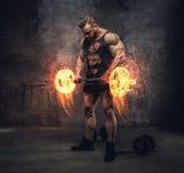 Bodybuilder mienia płonący barbell zdjęcia royalty free