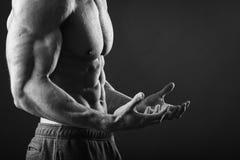 Bodybuilder montrant à le sien la presse Image stock