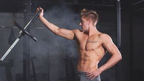 Bodybuilder musculaire caucasien fléchissant des plats de poids sur la barre de fer dans le gymnase, mouvement lent clips vidéos