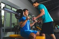 Bodybuilder musculaire d'athlète et entraîneur personnel dans la formation de gymnase avec le barbell photos libres de droits