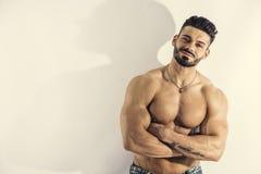 Bodybuilder musculaire se penchant contre le mur blanc Image libre de droits