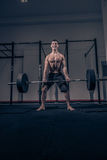 Bodybuilder muscular deadlift, dark indoors gym, shouting scream. One young adult man, bodybuilder muscular deadlift weights bar shouting screaming, dark indoors Royalty Free Stock Image