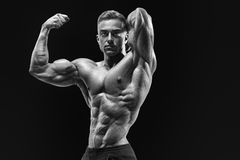 Bodybuilder with muscular physique looking at camera showing bic Stock Photos