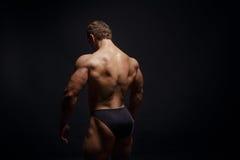 Bodybuilder musculeux montrant le sien arrière Photographie stock libre de droits