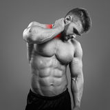 Bodybuilder neck pain. Muscular man suffering from neck pain. Front view over gray background stock photography