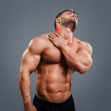 Bodybuilder neck pain. Muscular man suffering from neck pain. Front view over gray background stock photos