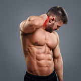 Bodybuilder neck pain. Muscular man suffering from neck pain. Front view over gray background stock images
