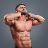 Bodybuilder neck pain. Muscular man suffering from neck pain. Front view over gray background royalty free stock photos