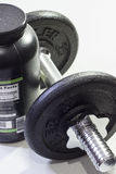 Bodybuilder needs. A pound of supplement and dumbell Royalty Free Stock Images