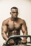 Bodybuilder noir musculaire s'exerçant sur le vélo stationnaire dans le gymnase Photographie stock libre de droits