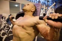 Bodybuilder obliquamente che fa weightlifting in ginnastica fotografia stock libera da diritti