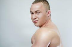 Bodybuilder in olie op een grijze achtergrond Stock Fotografie