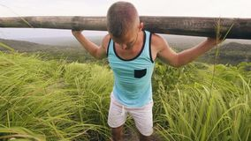 Bodybuilder opleidingshelling met zware houten bar op schouders op wild aardlandschap Mens die houtbar voor gewicht gebruiken stock videobeelden