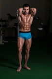 Bodybuilder Performing Front Abdominal Thigh Poses Stock Images