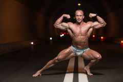 Bodybuilder Performing Front Double Biceps Poses In Tunnel Royalty Free Stock Photography