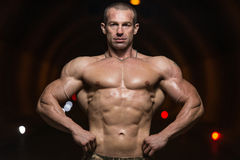 Bodybuilder Performing Front Lat Spread Poses In Tunnel Royalty Free Stock Photos