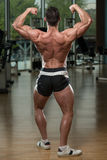 Bodybuilder Performing Rear Double Biceps Pose Royalty Free Stock Image