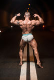 Bodybuilder Performing Rear Double Biceps Poses In Tunnel Stock Images