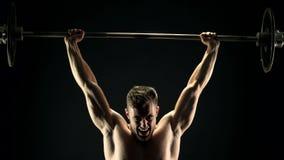 Bodybuilder persévérant soulevant le barbell lourd banque de vidéos