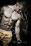 Bodybuilder picking up weights in the gym Royalty Free Stock Photo