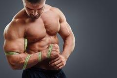 Bodybuilder pomiarowi bicepsy z taśmy miarą Zdjęcia Royalty Free