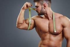 Bodybuilder pomiarowi bicepsy z taśmy miarą obraz stock