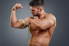 Bodybuilder pomiarowi bicepsy z taśmy miarą Fotografia Royalty Free