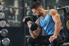 Bodybuilder pompuje jego bicepsy z dumbbell w gym obraz stock