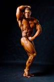 Bodybuilder posing on black background Stock Images