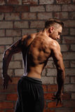 Bodybuilder Posing. Dorsi. Bodybuilder posing at a brick wall. The athlete ahead of the competition. Drying. Relief and sculptural body muscles. Concept of Stock Image