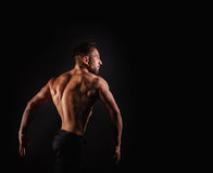 Bodybuilder Posing. Dorsi muscle. Bodybuilder posing on a black background. Dramatic portrait of an athlete. Drying. Relief and sculptural muscles of the body Stock Photo