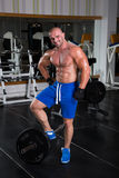 Bodybuilder posing in the gym. Bodybuilder in the gym preparing for the exercise Royalty Free Stock Images