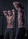 Bodybuilder posing, looking at himself, double mirror image. Muscular shirtless body Royalty Free Stock Photos