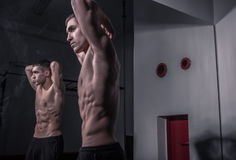 Bodybuilder posing, mirror image, dark indoors gym. One young adult man, bodybuilder posing, mirror image, dark indoors gym Stock Photo