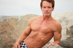 Bodybuilder posing on the rocks Stock Images