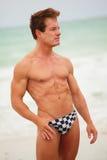Bodybuilder posing in speedos Royalty Free Stock Images