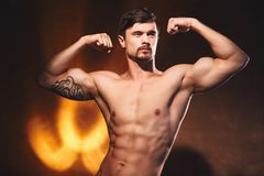 Bodybuilder posing in studio. Handsome power athletic guy male. Studio portrait of handsome young strong man  posing in studio Royalty Free Stock Photography