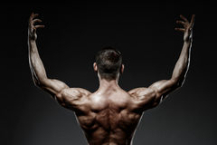 Bodybuilder posing and turned his back Royalty Free Stock Photos