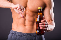 Bodybuilder pours beer Royalty Free Stock Image