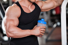 Bodybuilder protein shake. Young professional bodybuilder in the gym, drinking a protein shake Royalty Free Stock Images