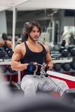 Bodybuilder pulling cable on weightlifting machine. Male bodybuilder wearing workout outfit while pulling cable on weightlifting machine royalty free stock photo