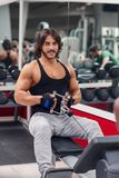 Bodybuilder pulling cable on weightlifting machine. Male bodybuilder wearing workout outfit while pulling cable on weightlifting machine and looking at camera stock photos