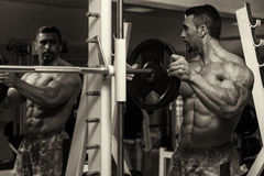 Bodybuilder Putting Weights On Bar In Gym Royalty Free Stock Images