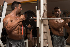 Bodybuilder Putting Weights On Bar In Gym Stock Photo