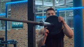 Bodybuilder putting on weights on the barbell stock footage